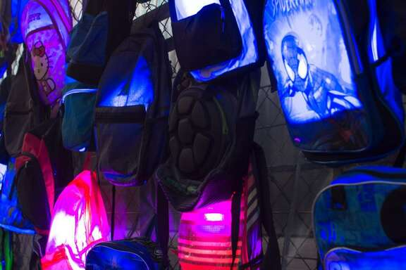 "A detail of Nathaniel Donnett's ""Acknowledgement: The Historic Polyrhythm of Being(s),"" a public artwork made with LED lights, photographs and the used backpacks of youth in Third, Fourth and Fifth Wards, installed along 120 feet of construction fencing around the Contemporary Arts Museum Houston."