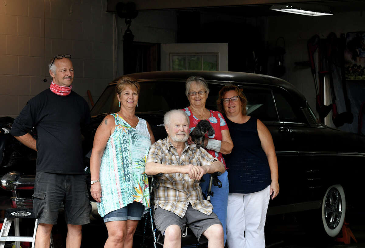 James Kennedy, 80, center, is joined by family members; James Kennedy, left, Kathy Becker, wife Charlotte, second from right, and Tracy Davey, right, as they gather around his classic '53 Mercury on Wednesday, July 22, 2020, at his garage in Halfmoon, N.Y. Kennedy is recovering from a heart condition through the aid of home health care. His family chose to treat him at home after fearing hospital visitation bans and a potential outbreak of COVID-19. (Will Waldron/Times Union)