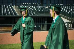 Graduating seniors from H. H. Dow High School celebrate during a socially distanced commencement ceremony Friday, July 24, 2020 at Dow Diamond. (Katy Kildee/kkildee@mdn.net)