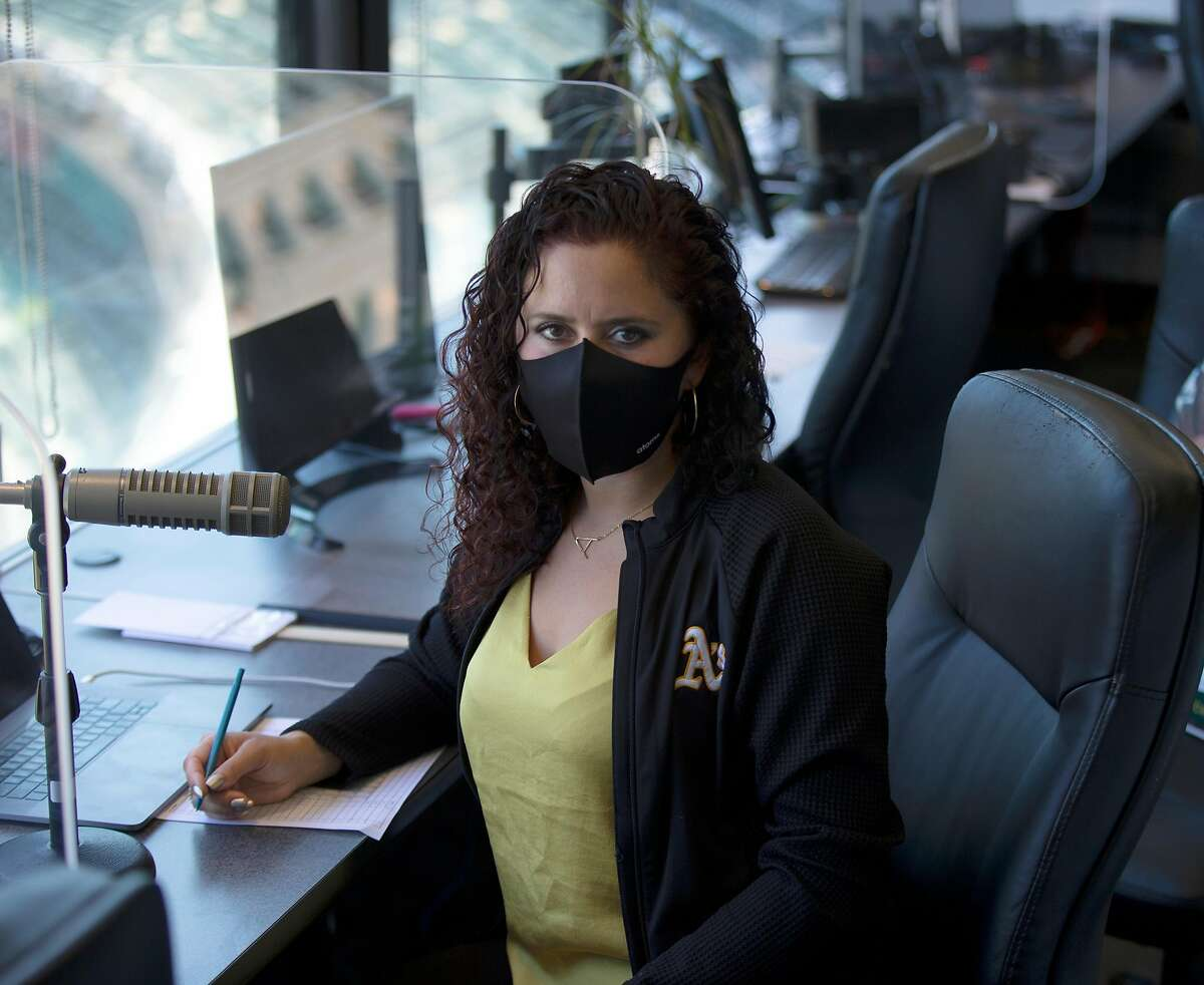 Oakland Athletics public address announcer Amelia Schimmel poses for a photograph in the announcer's booth at the Coliseum before the start of the regular season Thursday, July 23, 2020 in Oakland, Calif. Schimmel is filling in for long-time A's PA man Dick Calahan during the coronavirus pandemic.