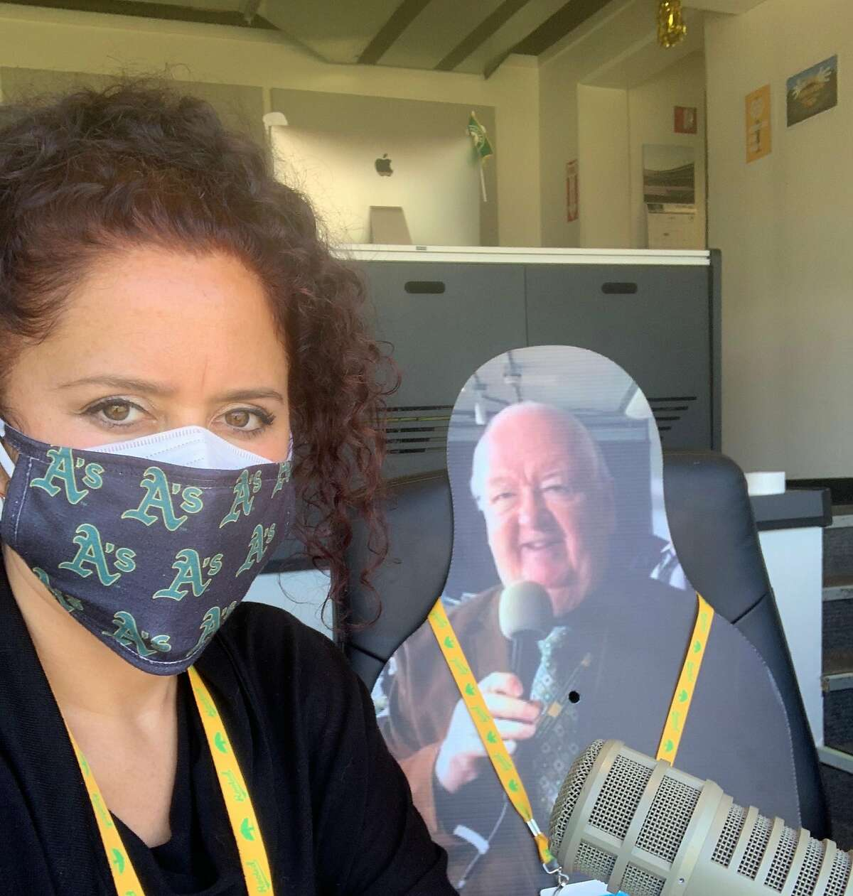 A's executive producer of ballpark entertainment Amelia Schimmel is filling in while PA announcer Dick Callahan (seen as a cutout) is out for the season.