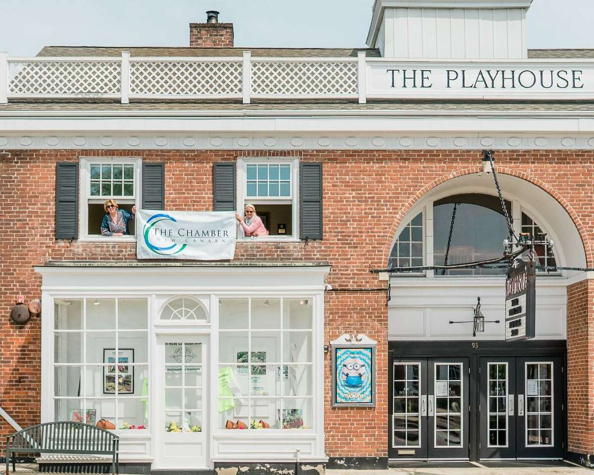 New Canaan Chamber of Commerce Marketing Associate Laura Budd is taking over for the chamber's current Executive Director Tucker Murphy September 8, 2020, when Murphy becomes the town's administrative officer for the retiring one, Tom Stadler. Budd, and Murphy previously hold a sign with the chamber's logo on it outside of the town's Playhouse, while they stand inside the town attraction, on its second floor.