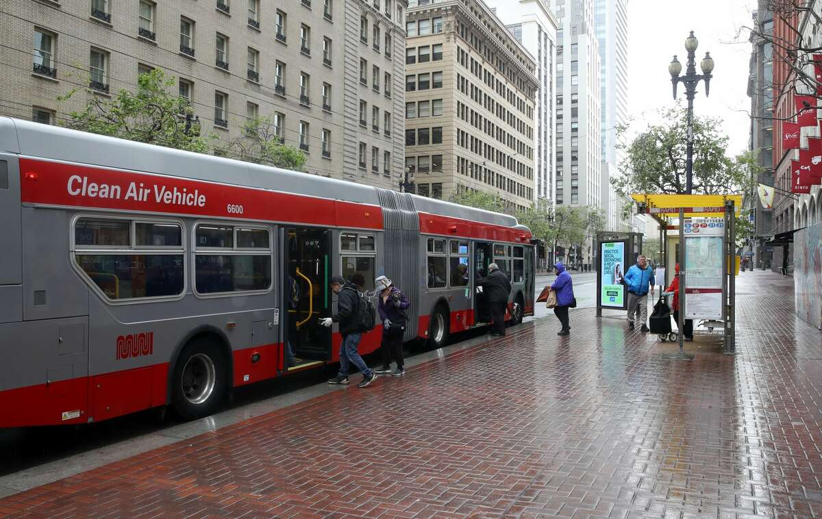 FILE - Passengers board a San Francisco MUNI bus during the coronavirus (COVID-19) pandemic on April 06, 2020 in San Francisco, California.