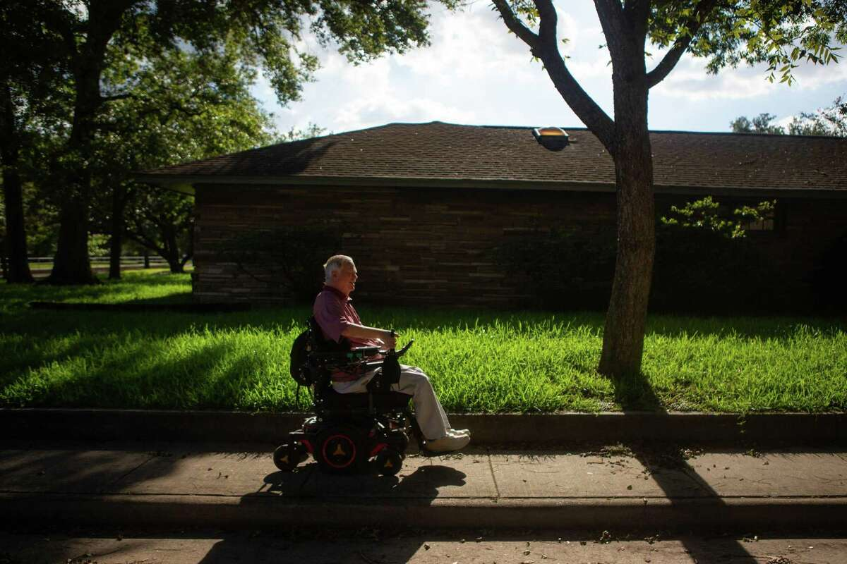 Lex Frieden rolls down the sidewalk in his neighborhood in Houston on Thursday, July 23, 2020. Frieden was instrumental with his help in writing the American's with Disabilities Act. A paraplegic, he has been a major disability rights activist in Houston and beyond since his early twenties when he first became paralyzed from a car accident and worked with a group to get the city to install lifts onto their their buses.