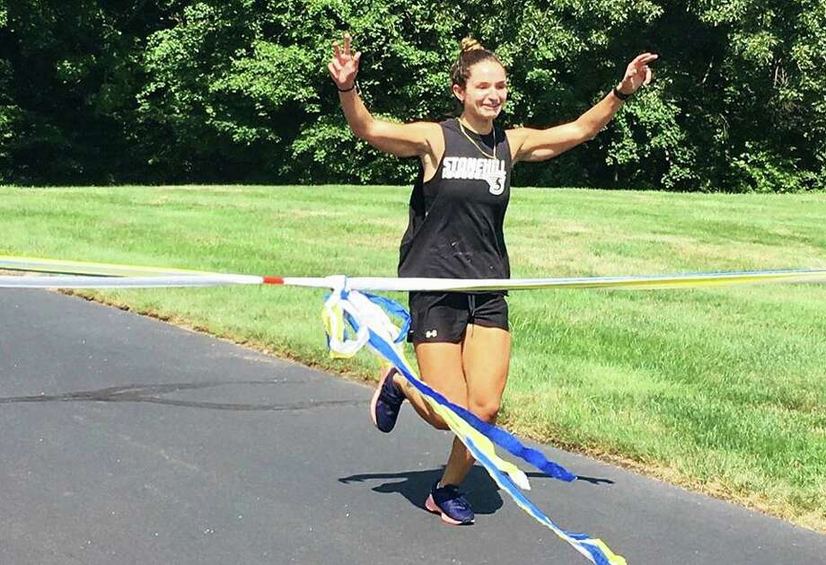 Middletown resident Alex Giardina ran a mile every hour for an entire day July 19 to raise money for The Borgen Project. Here, she crosses the finish line. Photo: Contributed Photo