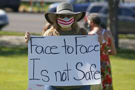 Kris Reddout, a 5th grade teacher, attends a Utah Safe Schools Mask-In urging the governor's leadership in school reopening during a rally Thursday, July 23, 2020, in Salt Lake City. Parents and teachers rallied at the Utah State Capitol Thursday morning to urge schools to enforce mask wearing and to implement other safety policies recommended by health officials as the state prepares to reopen classrooms this fall. (AP Photo/Rick Bowmer)