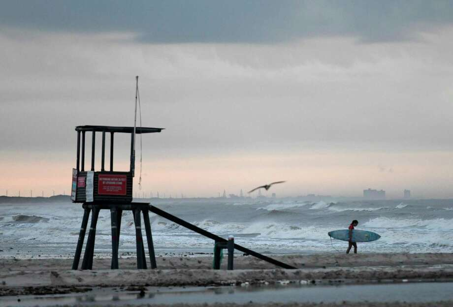 A surfer walks on the beach at J.P. Luby Park ahead of Tropical Storm Hanna, Friday, July 24, 2020, in Corpus Christi, Texas. The storm is expected to make landfall on Saturday. (Annie Rice/Corpus Christi Caller-Times via AP) Photo: Annie Rice, MBR / Associated Press / ©Annie Rice/Caller-Times