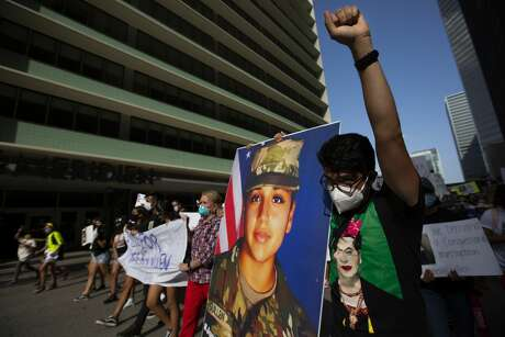 Ivan Lara, 28, marches carrying an photograph of Army Pfc. Vanessa Guillén, 20, on July 4, 2020, in Houston.