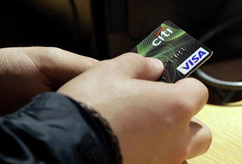 FILE - In this May 9, 2012, file photo, a Visa credit card is tendered at a store in New York's Times Square. Most of the time, using as little of your credit card limits as possible is better for your score. And yet using 1% of your available credit is slightly better than using 0%.  (AP Photo/Richard Drew, File) Photo: Richard Drew / Copyright 2017 The Associated Press. All rights reserved.