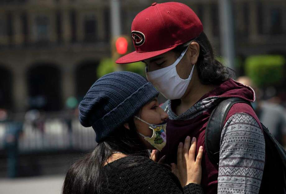 Protective face masks are a good idea — even with those you love, some experts say. Photo: Marco Ugarte, STF / Associated Press / Copyright 2020 The Associated Press. All rights reserved.
