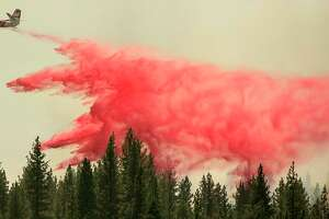 A CalFire aircraft drops fire retardant over the Hog fire, about 5 miles from Susanville, California, on July 21, 2020. (Photo by JOSH EDELSON / AFP) (Photo by JOSH EDELSON/AFP via Getty Images)