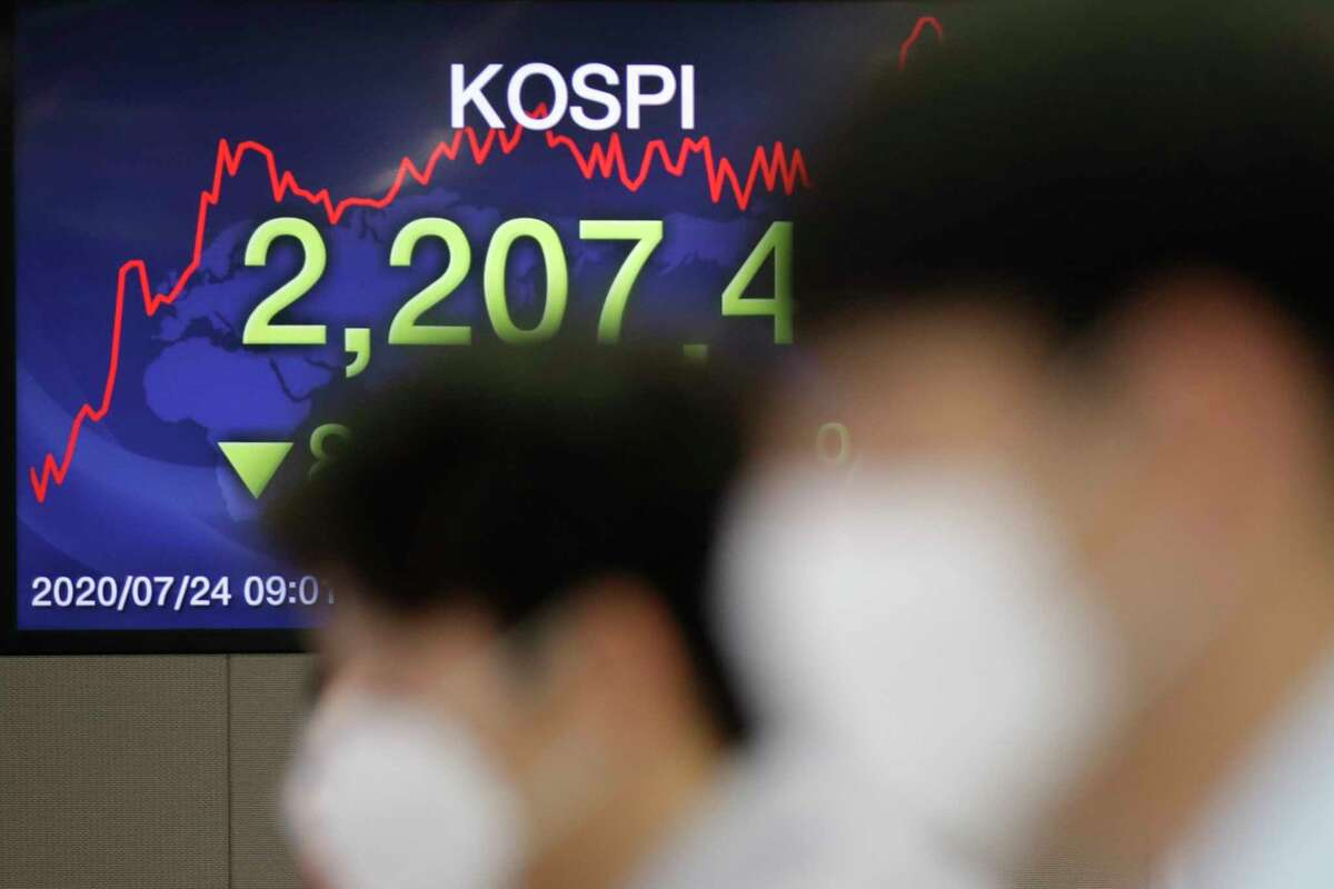 Currency traders watch computer monitors near a screen showing the Korea Composite Stock Price Index (KOSPI) at the foreign exchange dealing room in Seoul, South Korea, Friday, July 24, 2020. Worsening China-U.S. friction, worries over aid to Americans and U.S. businesses and a stumble on Wall Street combined to push shares in Asia lower on Friday. (AP Photo/Lee Jin-man)