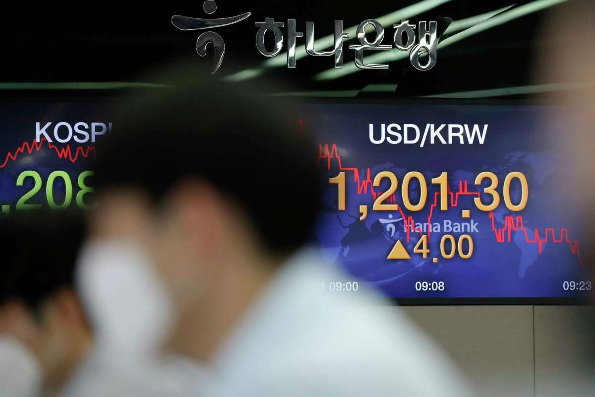 Currency traders watch computer monitors near screens showing the Korea Composite Stock Price Index (KOSPI), left, and the foreign exchange rate between U.S. dollar and South Korean won at the foreign exchange dealing room in Seoul, South Korea, Friday, July 24, 2020. Worsening China-U.S. friction, worries over aid to Americans and U.S. businesses and a stumble on Wall Street combined to push shares in Asia lower on Friday. (AP Photo/Lee Jin-man)