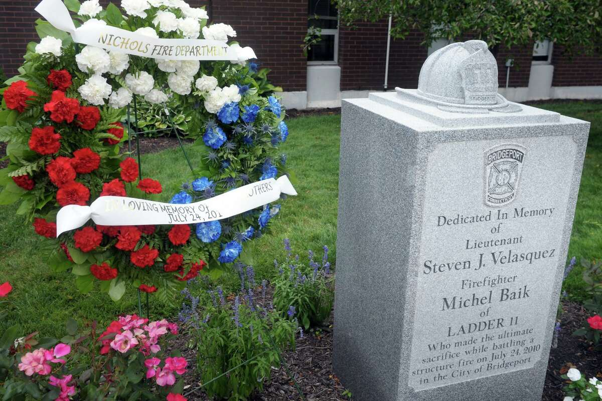 A wreath was in place Friday next to the memorial to Bridgeport firefighters Michel Baik and Lt. Steven Velasquez, at the fire station on Ocean Terrace. The firefighters died while fighting a fire on Elmwood Ave, in Bridgeport, Conn. ten years ago on July 24, 2010. Both men were assigned to Ladder Truck 11.