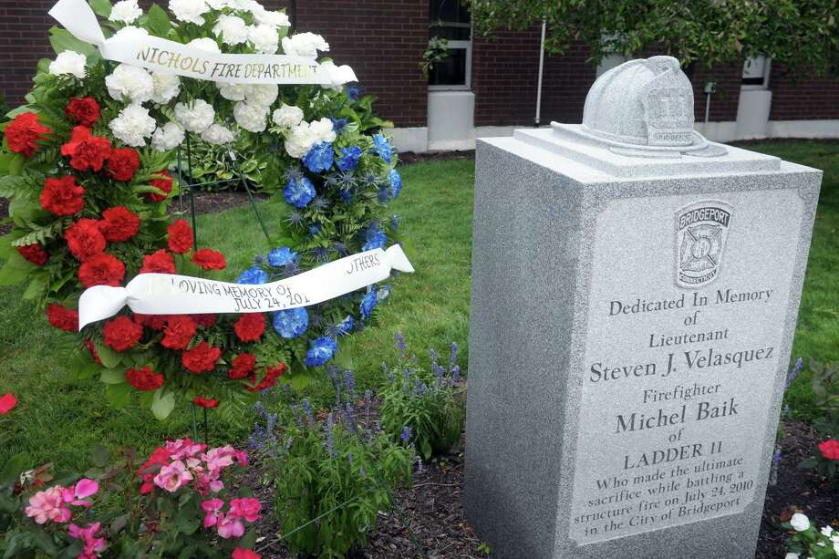 A wreath was in place Friday next to the memorial to Bridgeport firefighters Michel Baik and Lt. Steven Velasquez, at the fire station on Ocean Terrace. The firefighters died while fighting a fire on Elmwood Ave, in Bridgeport, Conn. ten years ago on July 24, 2010. Both men were assigned to Ladder Truck 11. Photo: Ned Gerard / Hearst Connecticut Media / Connecticut Post