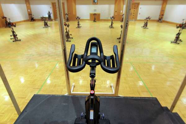 Exercise bikes are placed many feet apart for social distancing in a gym at the Jewish Community Center of Greater New Haven in Woodbridge, Conn., on Friday July 24, 2020. The center is closed for two hours each day to have extra cleaning to be done to protect members from the coronavirus.