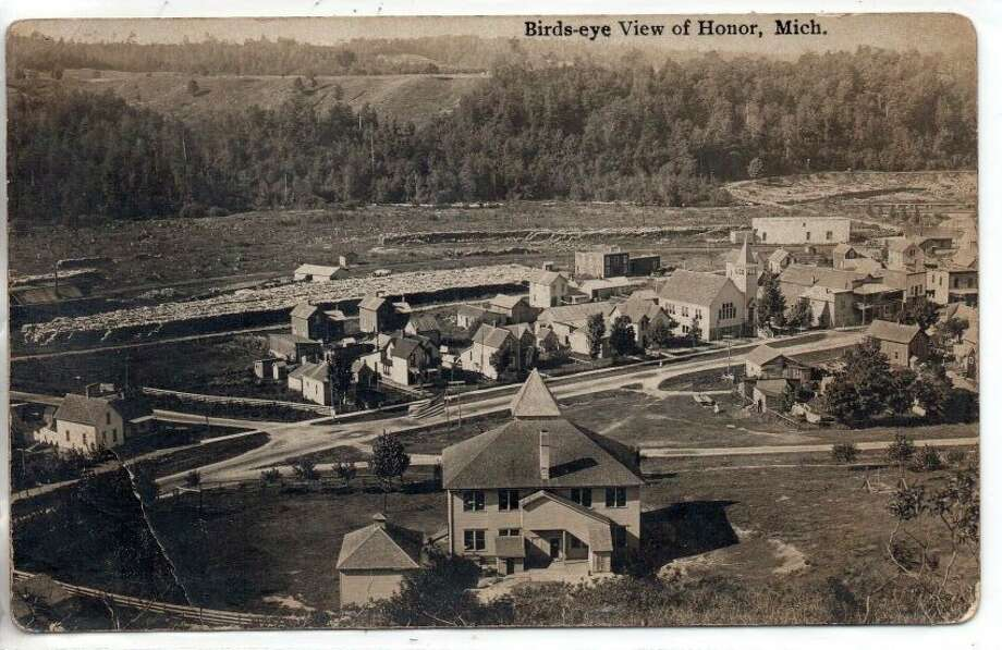 View of Honor early 1900's looking south, with a school in the foreground and the congregational church still present, as well as a massive pile of logs along the river bank at the Guelph Mill, which is just visible on extreme left. (Courtesy Photo)