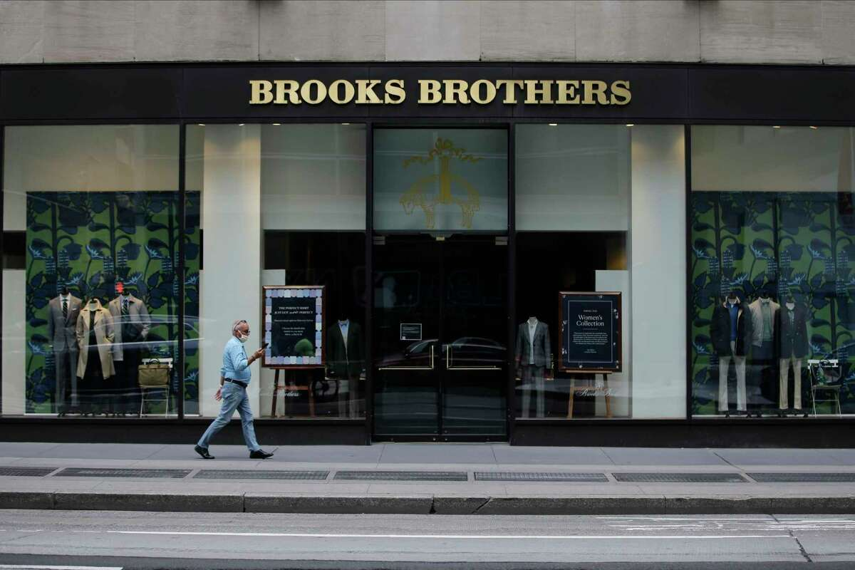 FILE - Pedestrians wearing protective masks walk past a Brooks Brothers location on July 8, 2020, in New York. A retail venture owned by licensing company Authentic Brands Group and mall owner Simon Property Group has agreed to buy Brooks Brothers for $305 million. The offer from Sparc Group LLC, announced late Thursday, July 23, has been designated as a a€œstalking horsea€ and therefore subject to court approval and any higher or better offers as part of the companya€™s ongoing auction process. (AP Photo/Frank Franklin II, File)