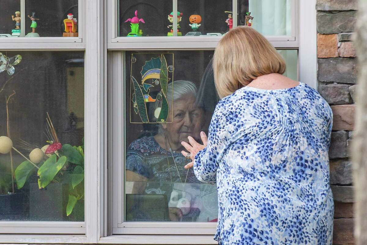 Winnie Byrnes visits with her daughter, Laurel Parker, at the window of her room in the Sunrise assisted living facility, Tuesday, May 5, 2020, in Cinco Ranch. Because of concerns about spreading coronavirus, family members are not able to visit their loved ones in the facility right now. The family often visits Winnie, talking by cell phone through the window and filling the bird feeder that is outside of her window.