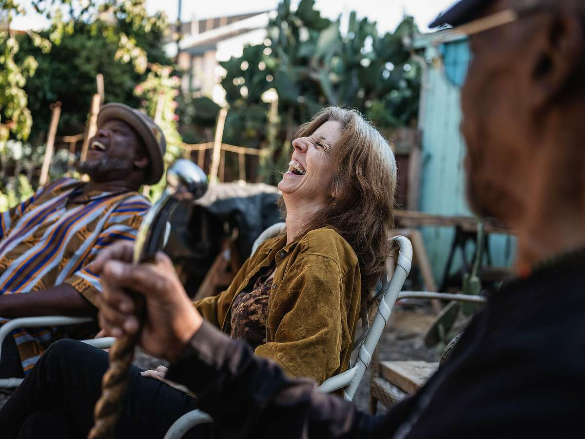 Zoe Mullery (middle) sits with former students Watani Stiner (right) and Troy Williams (left) sits in a community garden behind their home in Oakland Calif., on Thursday, July 23, 2020. The three met over a decade ago, at San Quentin prison, as Zoe led a creative writing program that Watani and Troy were both students in. Since the outbreak of Covid 19 many programs have been halted and volunteers have been forced to discontinue their efforts inside the prison.