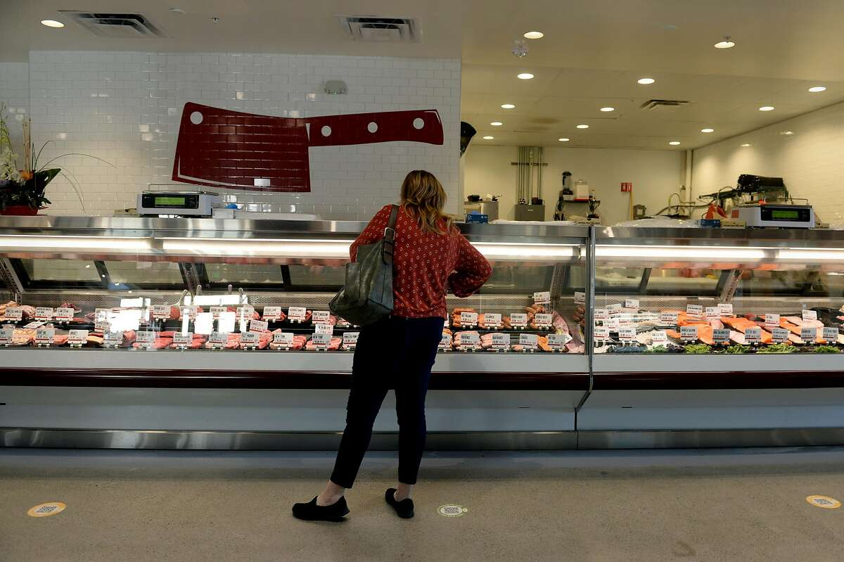Catherine Harrington orders swordfish and pork chops at Baron's Quality Meats & Seafood, part of the Castro Valley Market Place - open around two weeks - on July 24, 2020, in Castro Valley, Calif. So far, the market includes Castro Valley Natural Grocery, a grocery store focused on organic produce; Seven Hills Baking Co., a bakery with pastries and bread; and Baron's Quality Meats & Seafood, a butcher shop. Multiple restaurants, bars and other food shops are slated to join in the coming months.