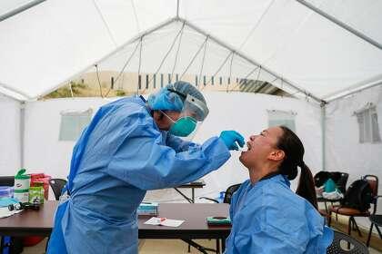 Nurse Rosemary MacLeod performed a coronavirus test on Nurse Pauline Tran at Laguna Honda Hospital in June.  Nurses are required to be tested every two weeks.