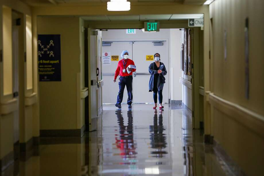Rodney Garrick (left) and Jennifer Carton-Wade walk down the hallway at Laguna Honda hospital in June. Photo: Gabrielle Lurie / The Chronicle