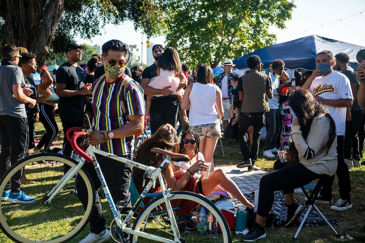 People enjoy food, dancing, and singing at the Juneteenth celebration at Lake Merrit in Oakland, CA on June 19, 2020.
