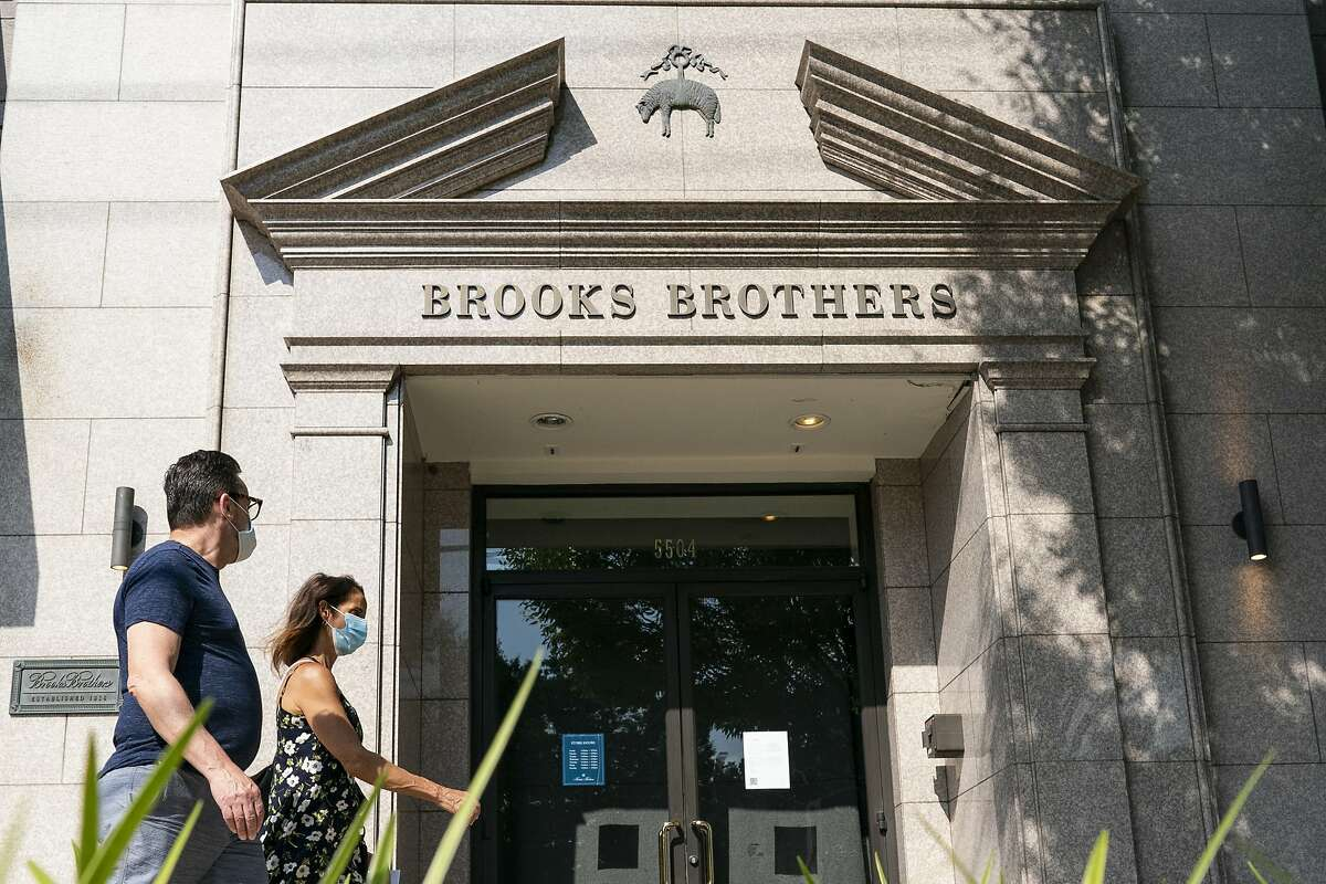 Pedestrians wearing protective masks walk past a Brooks Brothers store in Chevy Chase, Maryland, U.S., on Wednesday, July 8, 2020. Brooks Brothers Group Inc. filed for bankruptcy, felled by the coronavirus pandemic's impact on clothing sales and its own heavy debt load. Photographer: Alex Edelman/Bloomberg
