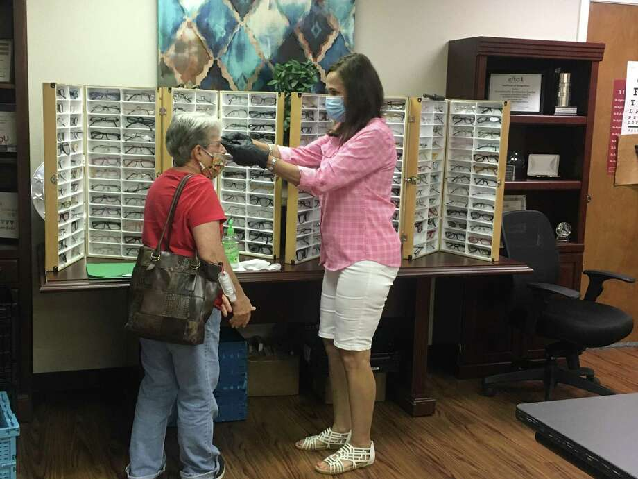 Lion Jane Copeland, right, assists a referral client with reading glasses during the Conroe Noon Lions Club Vision Screening held at the Community Assistance Center last week. Photo: Courtesy Photo