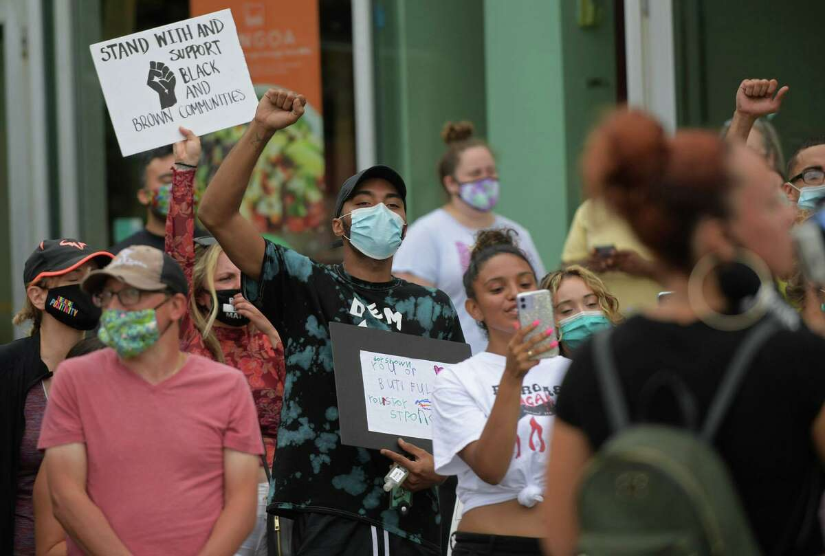 Protesters gather to support an employee at the Starbucks in Parker Harding Plaza, Dayshawn Rodriguez, center, Friday July 25, 2020, who alleged harassment by a customer at the cafe in Westport, Conn.