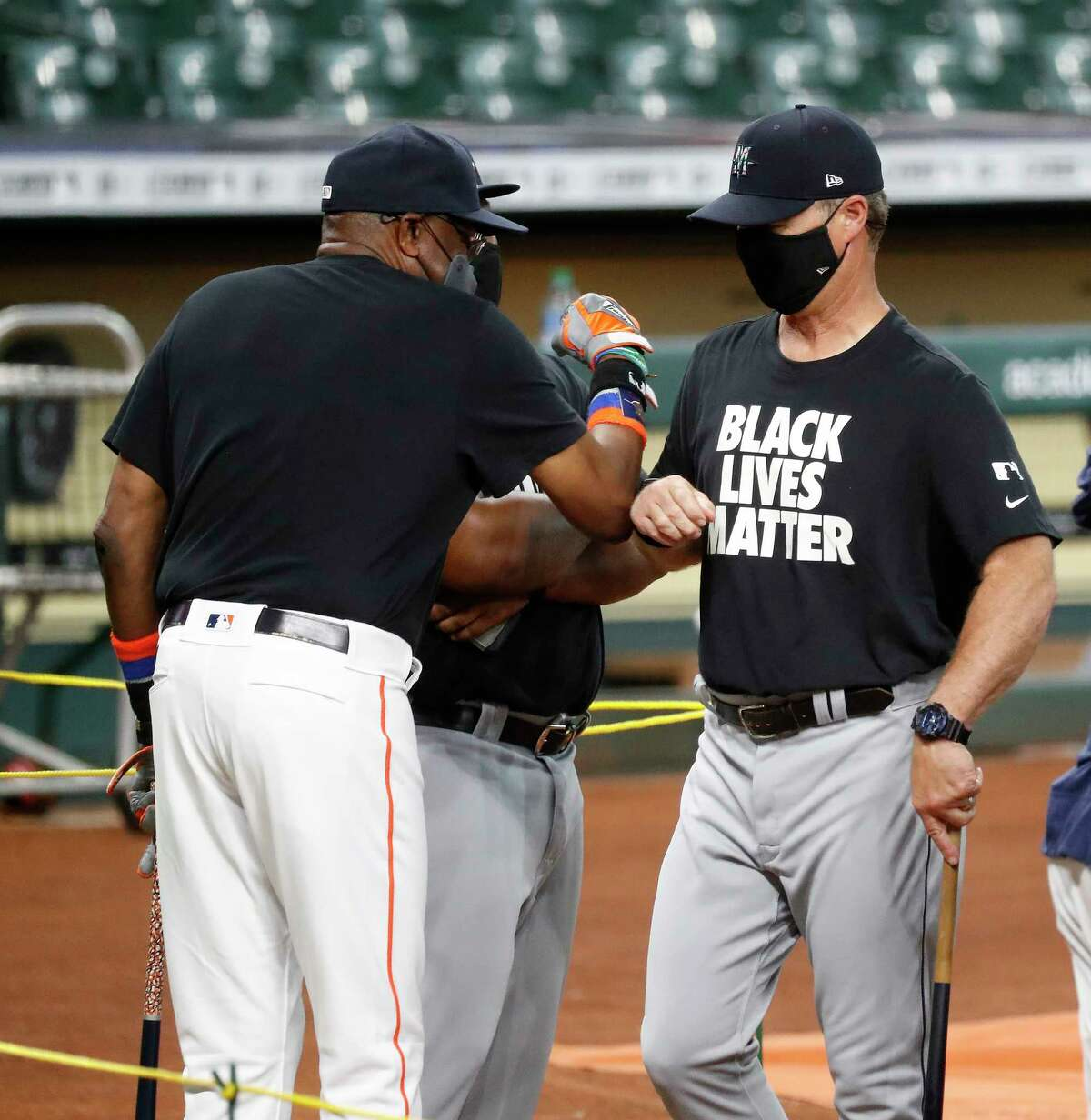 Houston Astros manager Dusty Baker elbow bumps Seattle Mariners manager Scott Servais during batting practice before the start of the Houston Astros Opening Day at Minute Maid Park, Friday, July 24, 2020, in Houston.