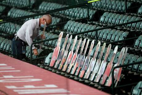 Thomas Bell, the Houston Astros Senior Director of Stadium Operations puts up more of the Astros player's family cutouts positioned in the front row behind the dugout before the start of the Houston Astros Opening Day at Minute Maid Park, Friday, July 24, 2020, in Houston.
