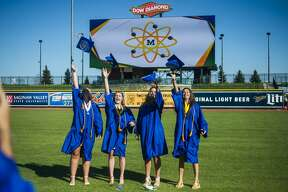 Graduating seniors from Midland High School celebrate during a socially distanced commencement ceremony Friday, July 24, 2020 at Dow Diamond. (Katy Kildee/kkildee@mdn.net)