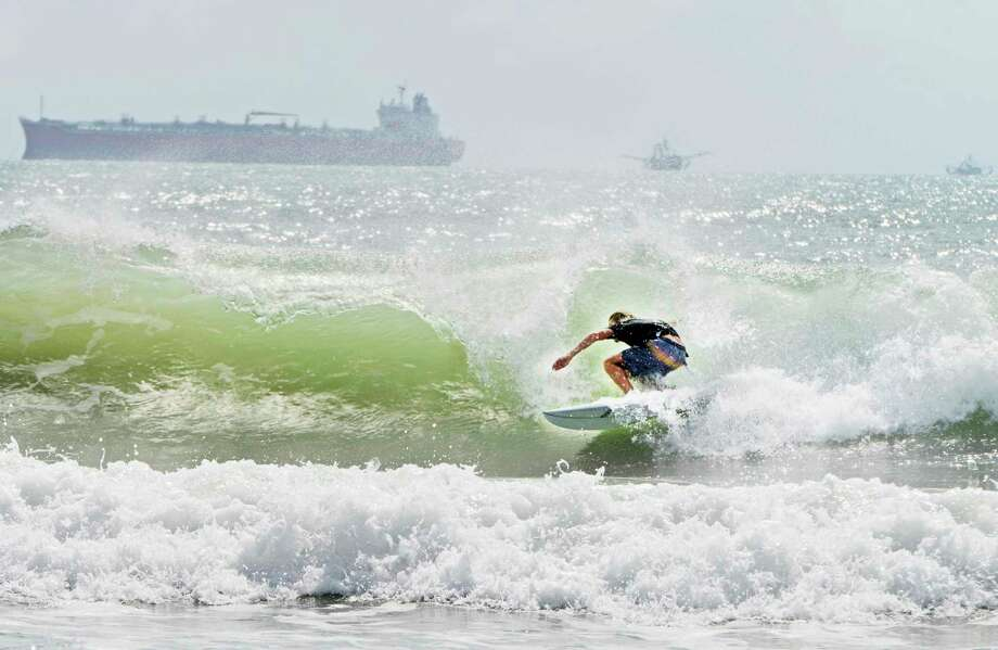 A surfer catches a barrel ride Friday, July 24, 2020, as swell waves approach the coast of South Padre Island, Texas, due to Tropical Storm Hanna approaching the Texas Gulf Coast. (Miguel Roberts/The Brownsville Herald via AP) Photo: Miguel Roberts, MBI / Associated Press / The Brownsville Herald