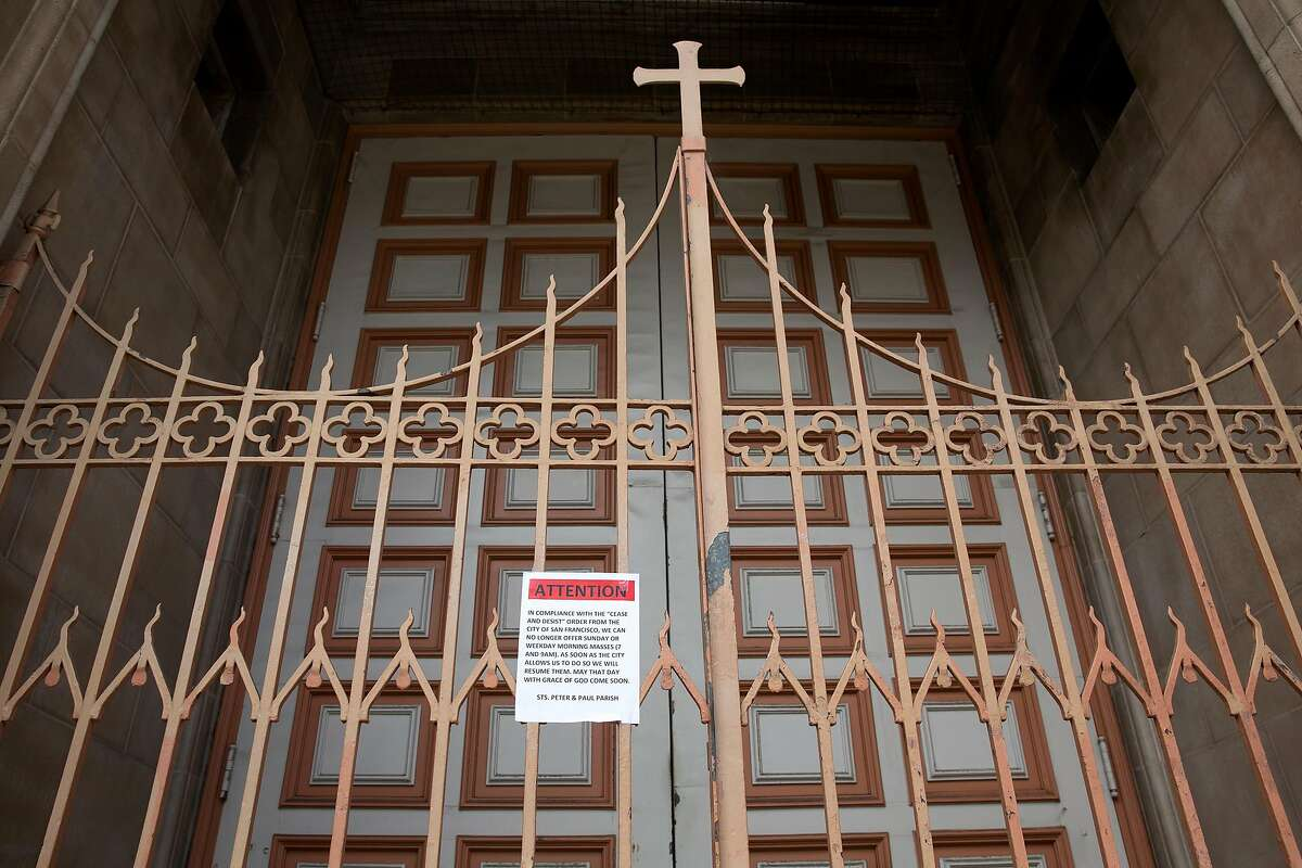 A sign stating Masses are canceled is posted on the front gates of Sts. Peter and Paul in North Beach.