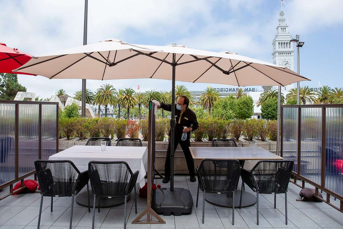 Jiang Rong, a buser at the Harborview Restaurant and Bar, cleans and disinfects partitions between tables at the restaurant in San Francisco, Calif. on Friday, July 24, 2020.
