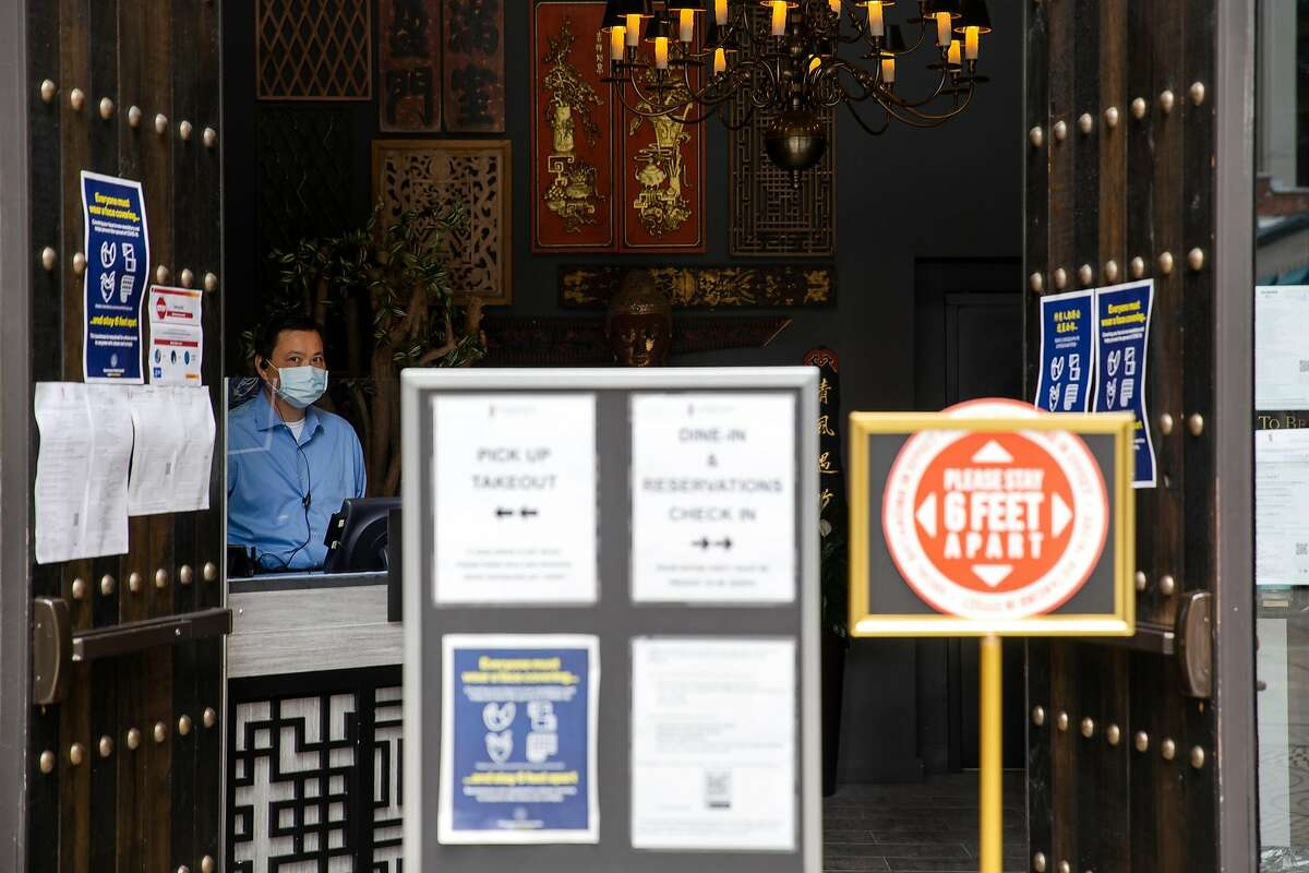 A host stands just inside the entrance to at the Harborview Restaurant and Bar surrounded by COVID-19 safety signs at the restaurant in San Francisco, Calif. on Friday, July 24, 2020.