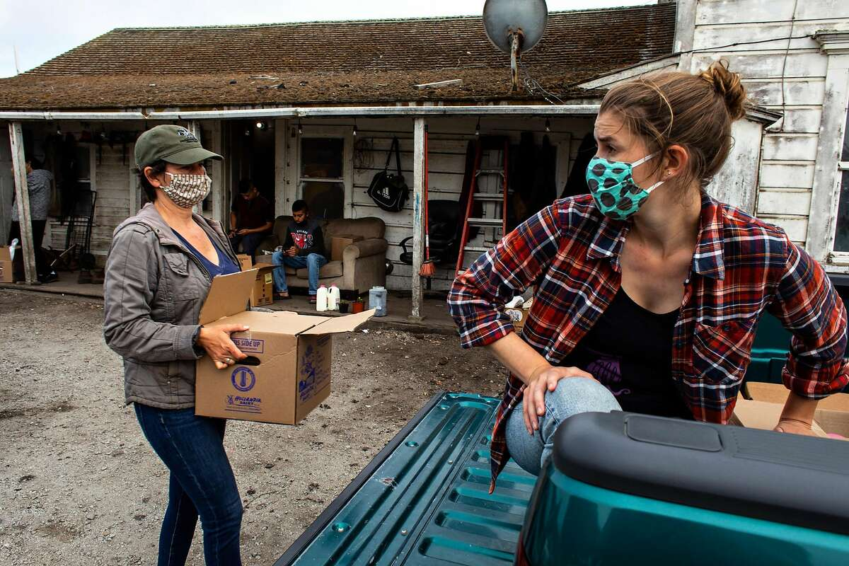 From left, Beth Pielert and Rachel Wright help bring food and PPE to farmworkers on Thursday, July 23, 2020 in Half Moon Bay, Calif. In San Mateo County, there is a large population of uninsured farmworkers who are at risk of contracting COVID-19 and only a limited amount of testing sites. Ayudando Latinos A Sonar is a group that has been working to distribute PPE and other resources to farmworkers in the area during the pandemic.