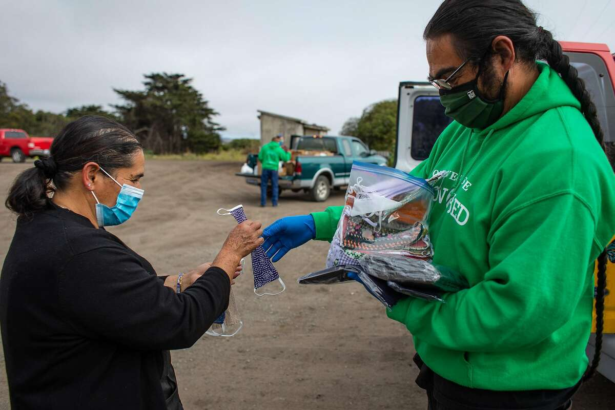 Joaquin Jimenez, right, gives a mask to Lola Serrano on Thursday, July 23, 2020 in Half Moon Bay, Calif. In San Mateo County, there is a large population of uninsured farmworkers who are at risk of contracting COVID-19 and only a limited amount of testing sites. Ayudando Latinos A Sonar is a group that has been working to distribute PPE and other resources to farmworkers in the area during the pandemic.