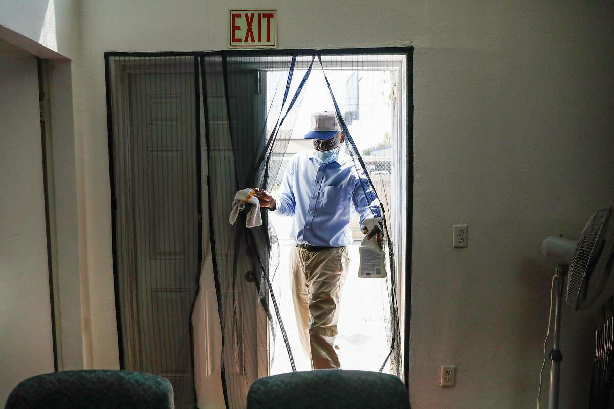 Curtis Louis a deacon at the Bible Way Missionary Baptist church walks through the side entrance as he sanitizes the church due to the coronavirus on Wednesday, July 8, 2020 in Richmond, California.
