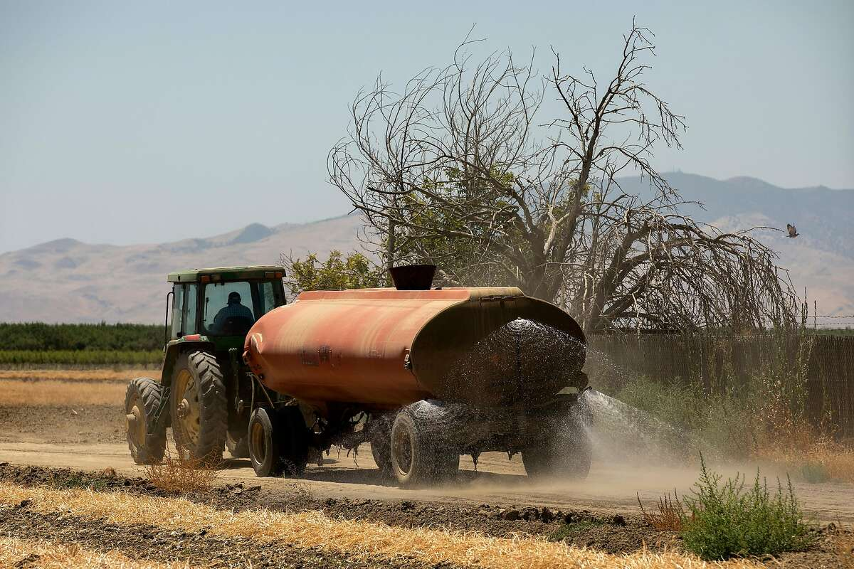 A truck sprays water in a field on Friday, July 24, 2020 in Cantua Creek, Calif.