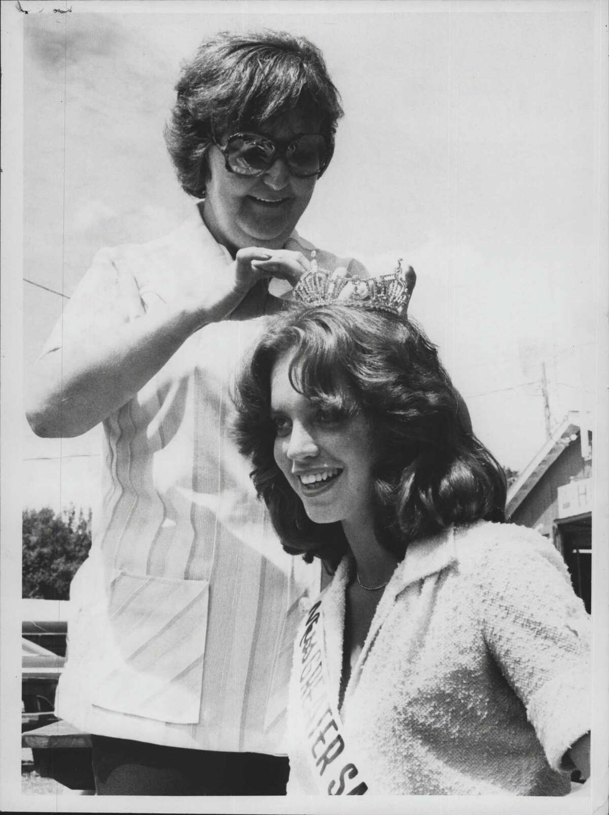 New York - Beverly Bell of Saratoga Springs, chaperone, with Joni Collura of Corinth, Miss Greater Saratoga County, getting crown adjusted after the ribbon cutting ceremony. July 25, 1988 (Times Union Archive)