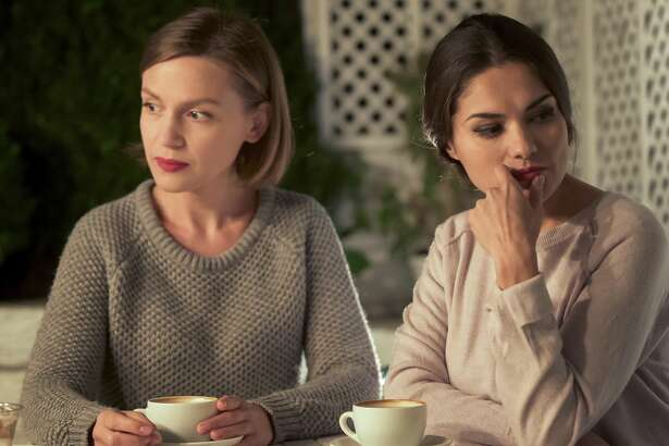 Two upset female friends sitting in cafe, relations conflict, misunderstanding