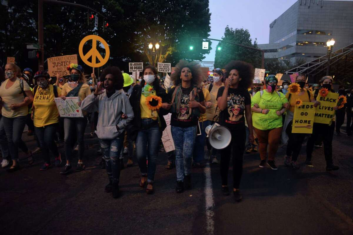 TOPSHOT - Demonstrators march to the Multnomah County Justice Center in Portland, Oregon, on July 23, 2020. - Police fired teargas and fought running battles with protesters in Portland in the latest night of demonstrations against police brutality and the deployment of federal troops to US cities. (Photo by Ankur Dholakia / AFP) (Photo by ANKUR DHOLAKIA/AFP via Getty Images)