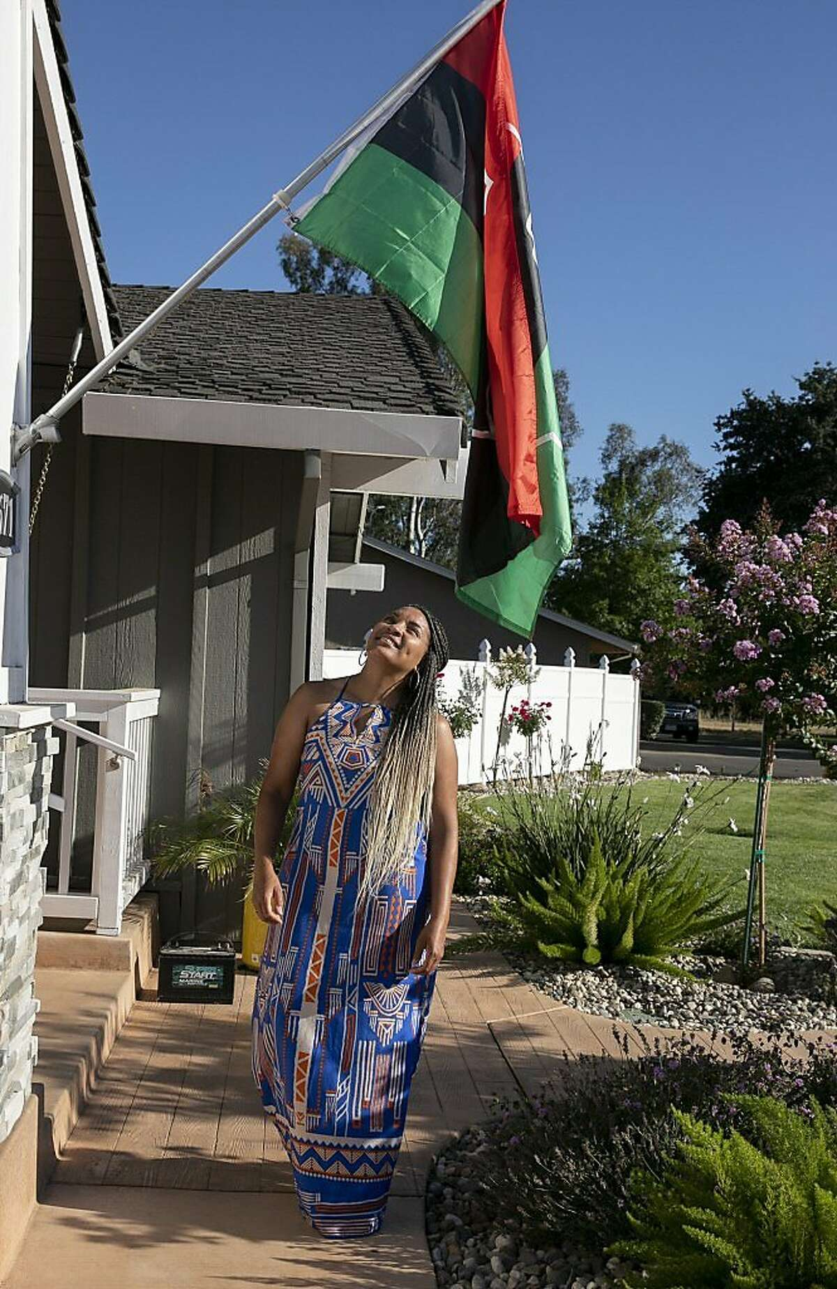 Sharie Wilson stands below the Pan African flag outside of her Elk Grove home on June 22, 2020. Wilson says that she raised the flag to celebrate Juneteenth as a way to help educate her neighbors about the holiday.