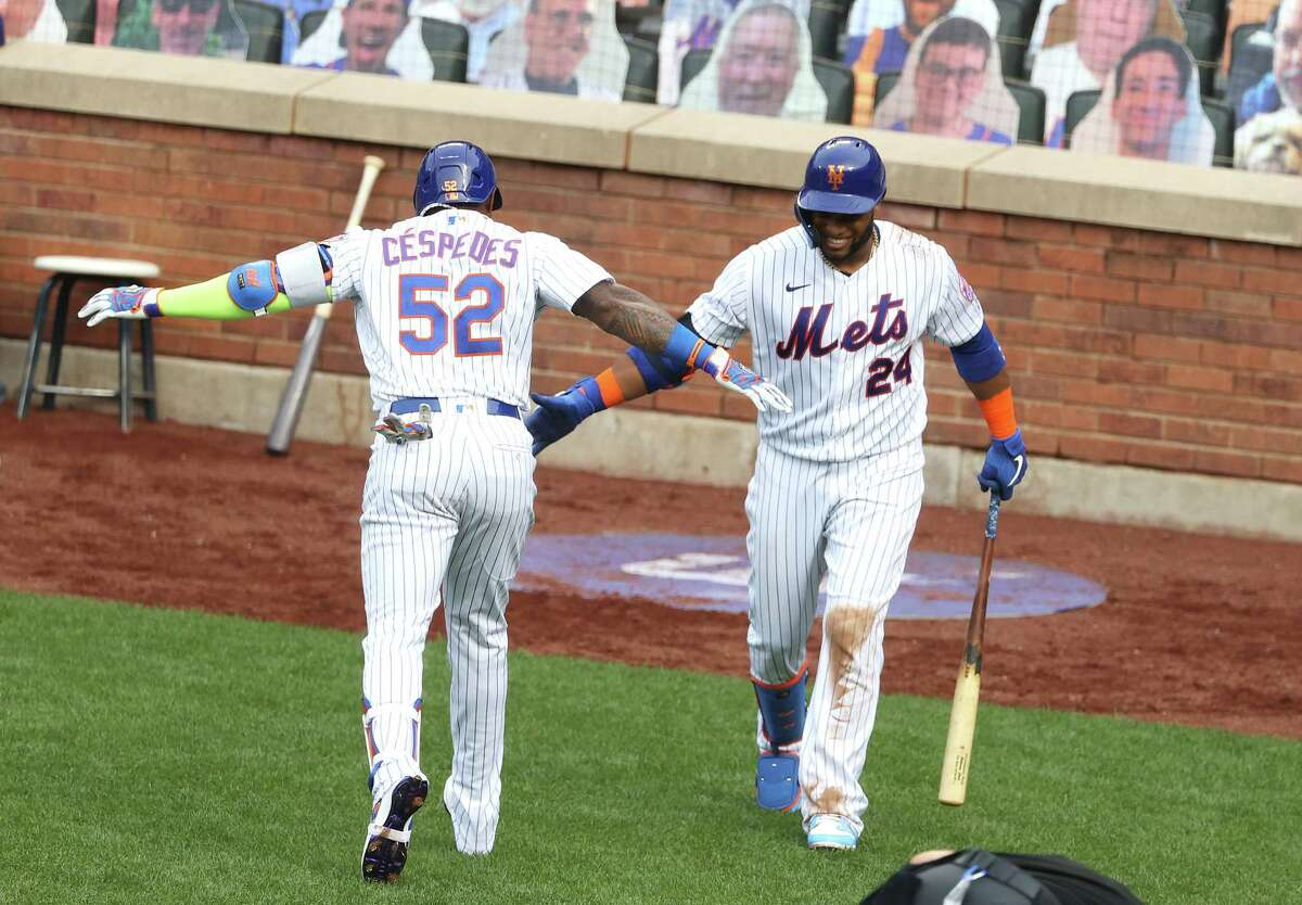 NEW YORK, NEW YORK - JULY 24: Yoenis Cespedes #52 of the New York Mets celebrates with Robinson Cano #24 after hitting a solo home run against the Atlanta Braves in the seventh inning during Opening Day at Citi Field on July 24, 2020 in New York City. The 2020 season had been postponed since March due to the COVID-19 pandemic. (Photo by Al Bello/Getty Images)