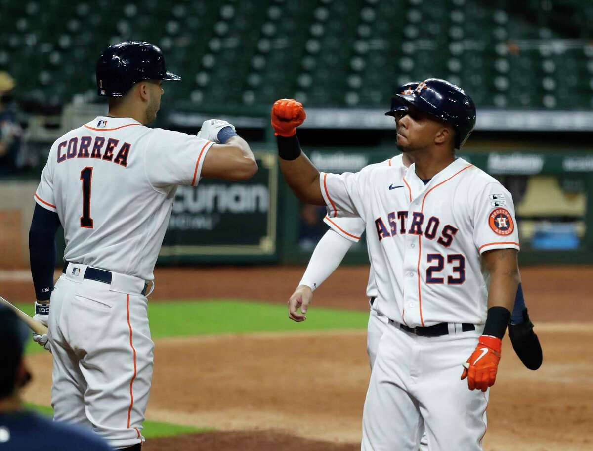 Houston Astros outfielder Michael Brantley celebrates with Carlos Correa after his three-run home run during the fifth inning of an MLB Opening Day at Minute Maid Park, Friday, July 24, 2020, in Houston.