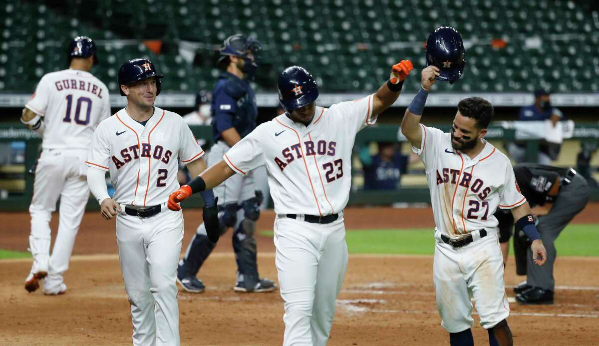 Houston Astros outfielder Michael Brantley celebrates with Jose Altuve after his three-run home run during the fifth inning of an MLB Opening Day at Minute Maid Park, Friday, July 24, 2020, in Houston.