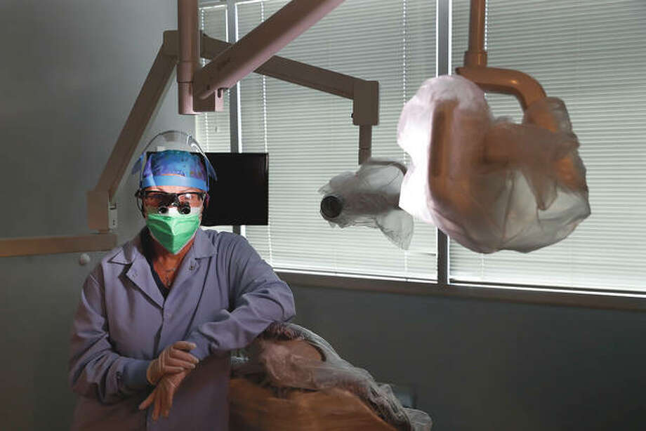Dr. Terri Tiersky dons full personal protective equipment — a double mask, face shield, gown and gloves — at her dentist office in Skokie. Photo: Charles Rex Arbogast   AP